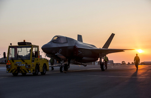 An F-35 jet is pictured against a sunset sky