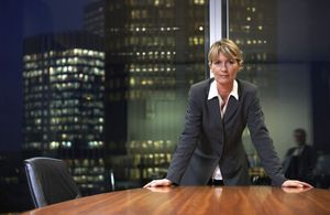Business woman standing at Board table in a corporate office