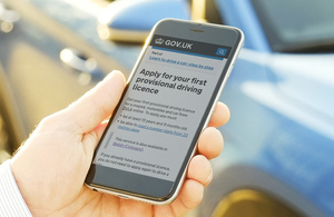 Mobile phone in someone's hand with the Apply for your provisional driving licence online service on the phone screen
