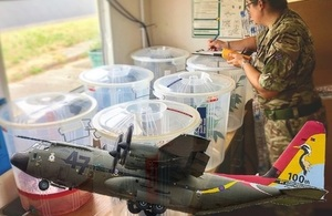 RAF Hercules superimposed over a member of RAF personnel dealing with waste products