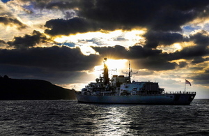 HMS Monmouth sailing with the backdrop of a sunrise