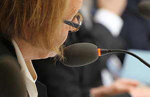 Inspector talking into a microphone.