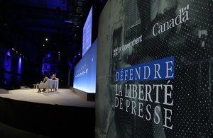 Media Freedom conference logo with panel seating in the distance