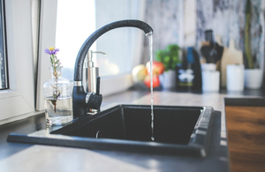 A black tap with water running from it, with a bottle with a flower in it and kitchen utensils in the background