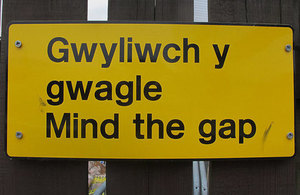 Mind the gap sign in Welsh and English.