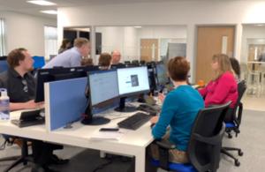 Photograph of people sitting around desks