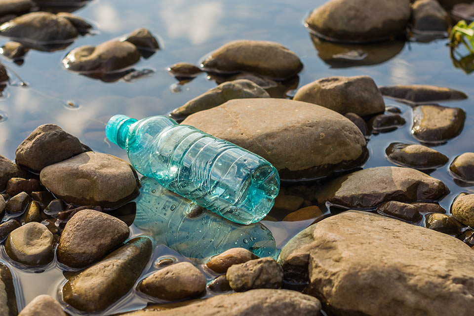 Plastic bottle sitting on rocks in water