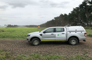 An Environment Agency vehicle parked beside a crop being spray irrigated. A line of trees is in the background.