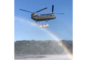 An RAF Chinook drops bags of aggregate into the Toddbrook Reservoir.