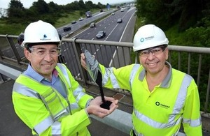 Martin Bolt, left, of Highways England and Paul Fleetham of Tarmac above the M1 in the East Midlands with the rubber granules being trialled in the road surface.