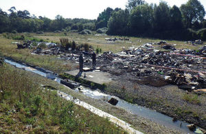 Picture shows two people inspecting rubbish dumped at site, some of which is in a stream in the foreground