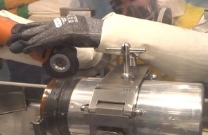 An operator working with a sealed glovebox while wearing several layers of protective gloves.