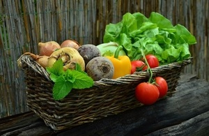 A basket of vegetables including lettuce, tomatoes and peppers in a brown basket.
