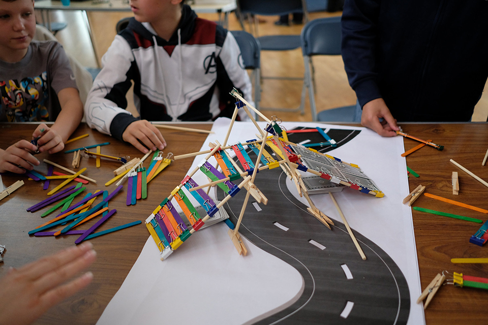 Image of a model bridge the children have built out of wooden sticks and paper clips.