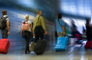 Airport passengers with luggage on walkway