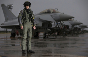 A pilot from 6 Squadron, RAF Lossiemouth in front of a line of Typhoon aircraft in full flying attire.