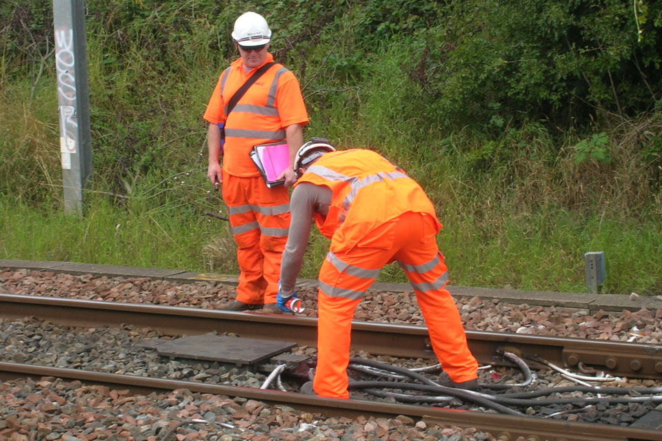 Railway workers fix severed cables
