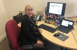 Gill Bragg sits at desk