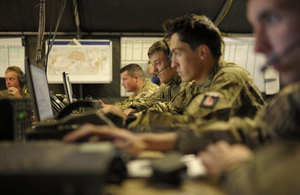 Image of battle headquarters with soldiers sitting at a desk some with headsets looking at computers.