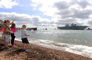 Children waving goodbye as HMS Queen Elizabeth leaves Portsmouth
