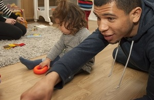 Child with nursery worker playing on floor