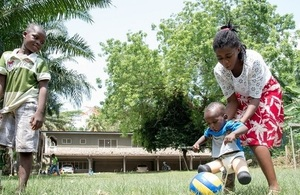 A child with prosthetic legs plays football with their mother