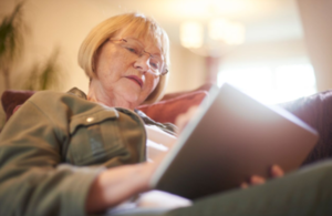 Woman sitting on sofa using tablet device