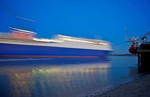 Cargo ship at dusk, passing close to shore, lights visible