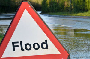 An image of a flood sign in front of a flooded road.