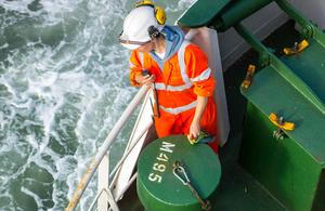 Female crew member working on deck of merchant ship