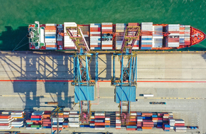 Aerial view of container ship in dock with cranes and freight containers