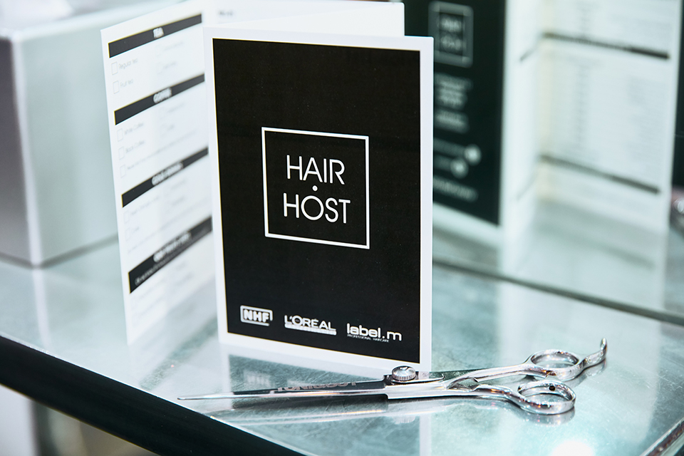 The Hair Host logo and scissors on a shelf.