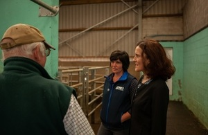 A picture of Theresa Villiers with Abi Reader and a farmer in a farm shed.