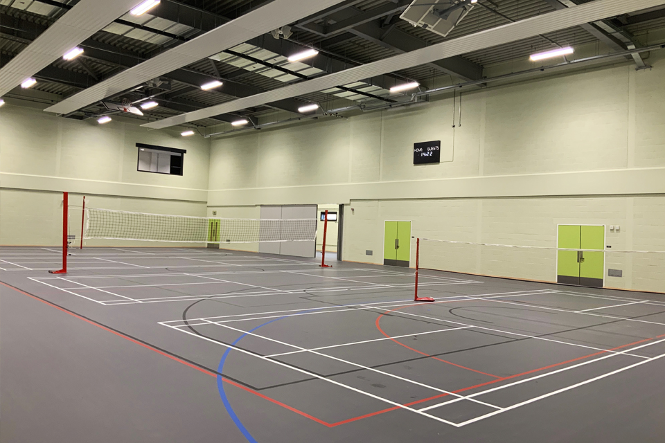 Photo shows the interior of the new sports centre at Worthy Down. Tennis courts are seen, and markings for basketball training.
