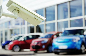 Photograph of a surveillance camera in front of parked cars