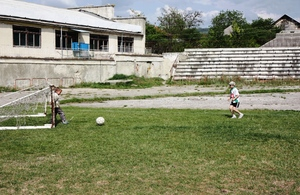 Kids playing football on an abandoned pitch.