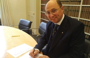 Image of Mark Watson-Gandy signing a document