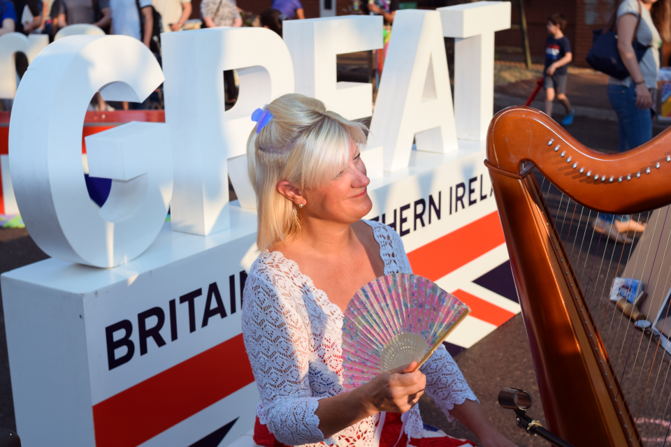 Harpist Anita Aslin fans herself next to her harp, in front of a GREAT Britain and Northern Ireland sign.