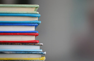 A stack of different coloured hardback books