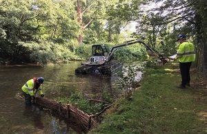 Here officers are re-profling a river with an amphibious excavator.
