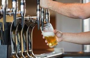 A bartender pulling a pint