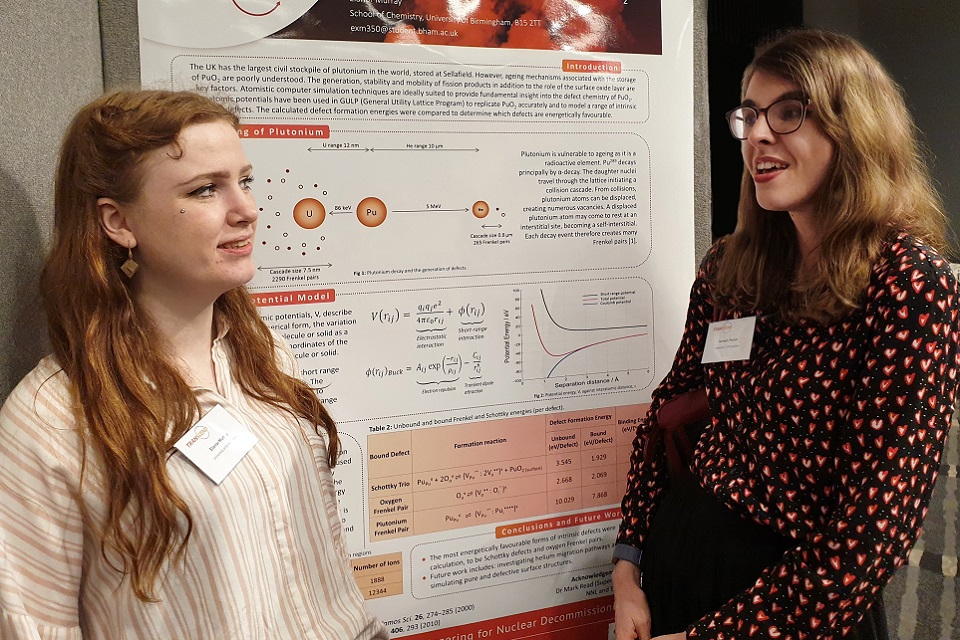 Two PhD students discussing a technical poster during a meeting of the TRANSCEND consortium