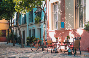 A European street scene with colourful building fronts, trees, table and chairs and a bicycle.