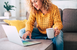 Woman sitting on sofa using laptop with cup in hand.