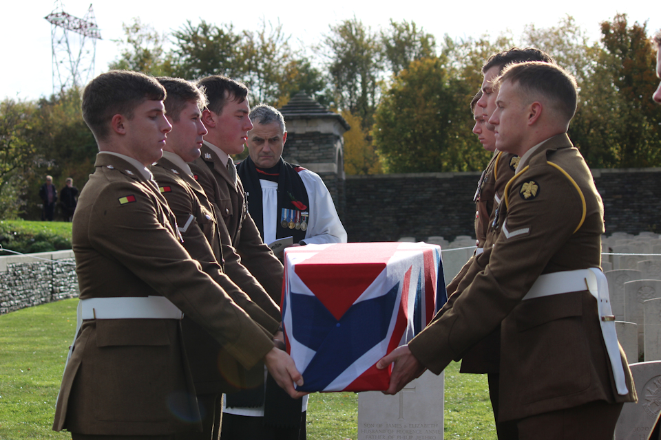 Soldiers from the 1st Battalion The Royal Anglian Regiment prepare to lower the coffin