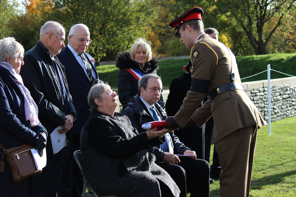 Lieutenant Piers Darby gives the Union Flag to Linda Cook, granddaughter of Lance Corporal Perkins