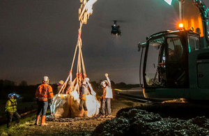 Image of chinook helicopted dropping sand bags, and a tractor with people standing by.