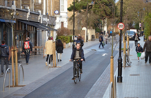 Cyclist on a cycle path passing shops and houses, people walking on pavements. A London mini Holland scheme.