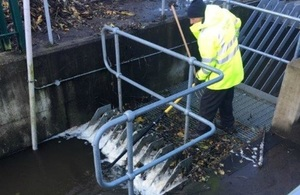 Image of man in high visibility jacket working on a flood gate