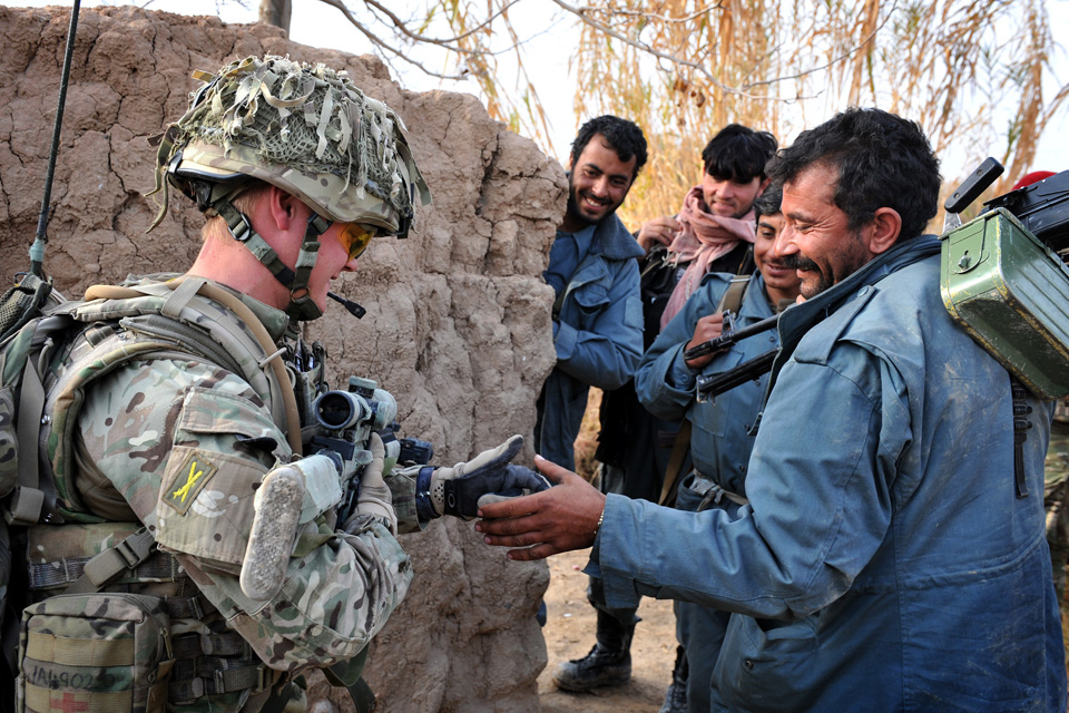 A British soldier shares a joke with members of the Afghan Uniform Police